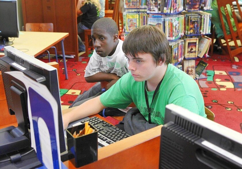 At the Serra Mesa library branch, Taft Middle School eighth-grader Deandre Leggette (left) and Kearny High ninth-grader Michael Patrick do an online search in the children's computer lab.