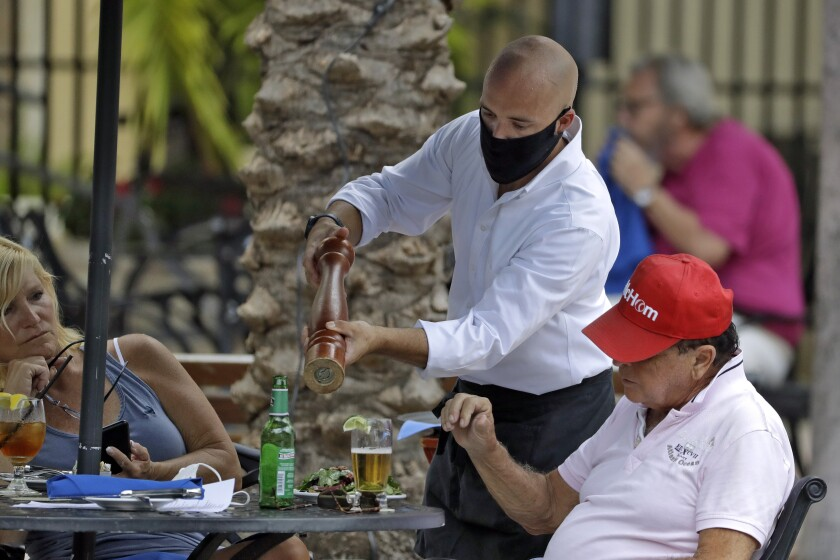 A food server wearing a protective face mask waits on customers at the Parkshore Grill restaurant Monday, May 4, 2020, in St. Petersburg, Fla. Several restaurants are reopening with a 25% capacity as part of Florida Gov. Ron DeSantis' plan to stop the spread of the coronavirus.