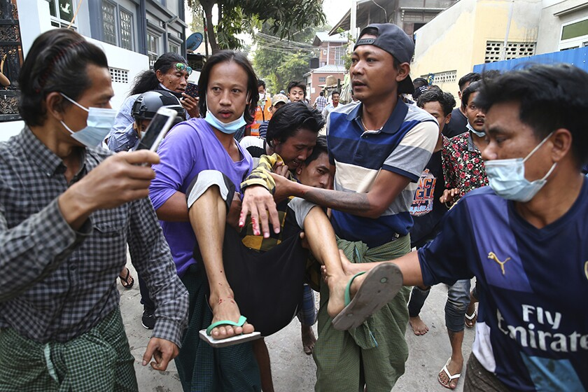 A man, left, holds his phone aloft as other people carry a man with blood on his fingers