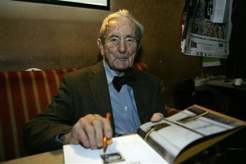 FILE - In this Nov. 20, 2009 file photo Leopold Hawelka signs a book in his famous cafe in downtown Vienna. Hawelka celebrates his 100th birthday, on Monday, April 11, 2011. Cafe Hawelka, which opened in 1939, is perhaps the most storied of hundreds of coffeehouses in Vienna where young and old spe