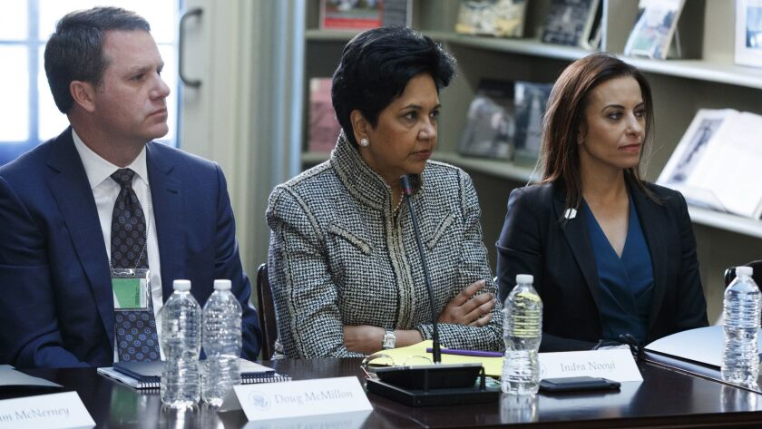 In this Aug. 11, 2017 photo, from left, Wal-Mart CEO Doug McMillon, Pepsi CEO Indra Nooyi, and Dina Powell, President Donald Trump's senior counselor for economic initiatives listen during a meeting with business leaders in Washington, D.C.