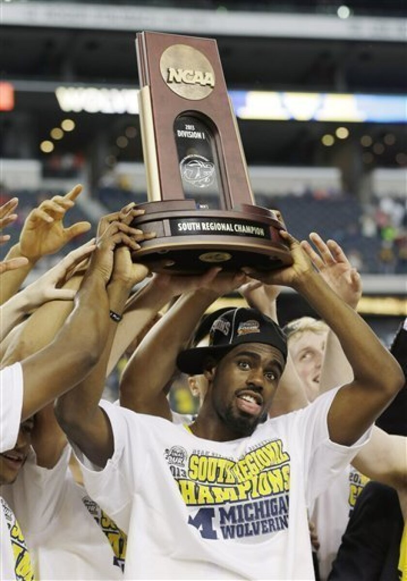 Michigan's Tim Hardaway Jr. holds the trophy after a regional final game against Florida in the NCAA college basketball tournament, Sunday, March 31, 2013, in Arlington, Texas. Michigan won 79-59 to advance to the Final Four. (AP Photo/David J. Phillip)
