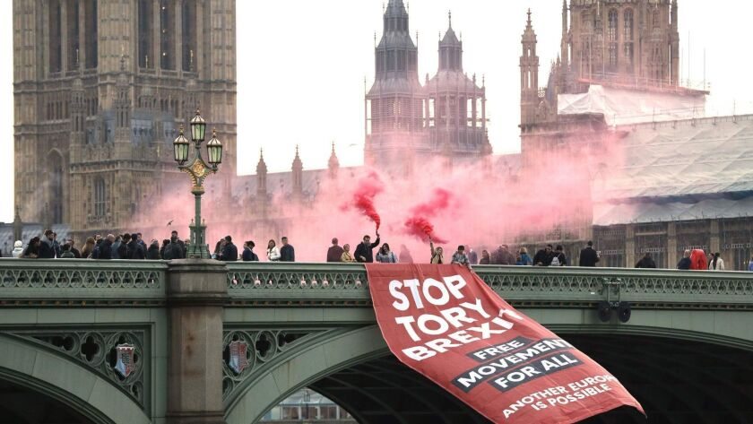 Anti-Brexit campaigners unfurl a banner on Westminster Bridge in front of the Houses of Parliament in London on Thursday.