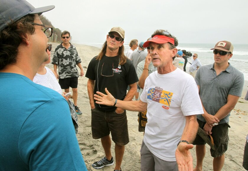 Encinitas resident Gerry Rahill, at right, who supports resident's rights to build seawalls, argues with the Surfrider Foundation's Tom Cook, close left.