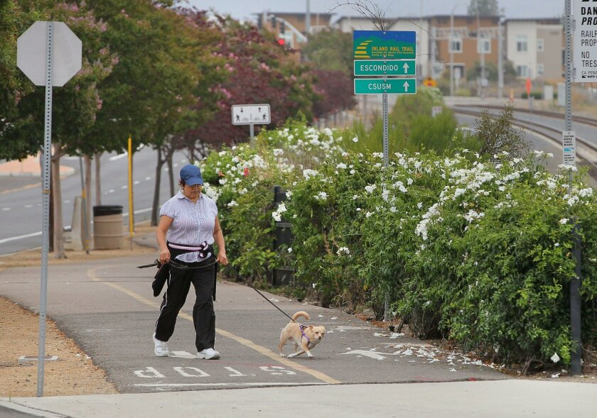 A pedestrian walks a dog on a paved portion of the Inland Rail Trail in San Marcos on Friday.