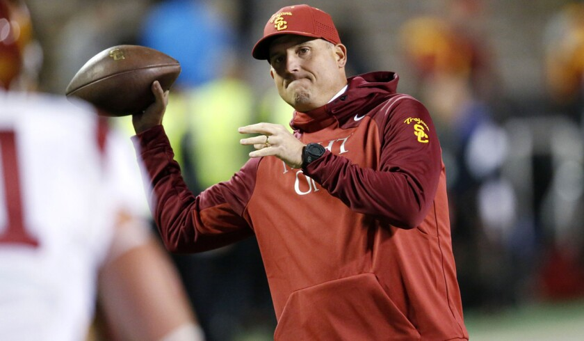 USC interim head coach Clay Helton gets ready to pass the ball on the sideline before a game against Colorado last Friday.