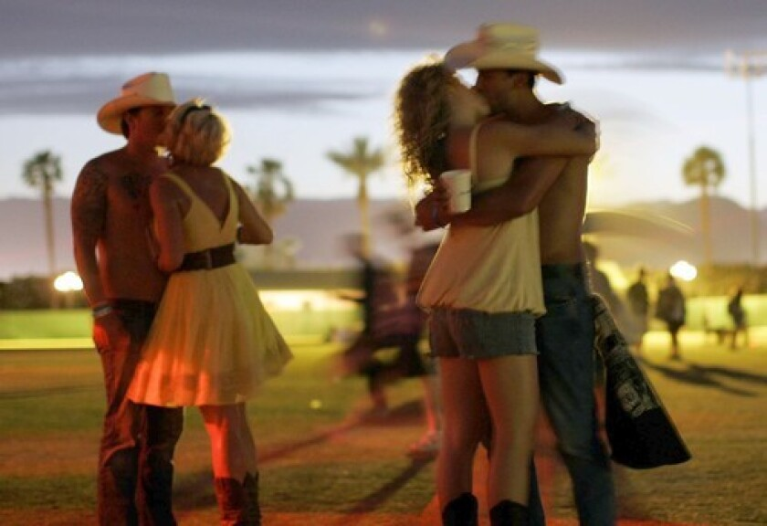 Couples kiss at a music festival.
