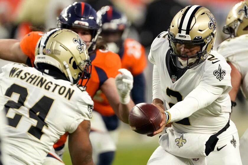 El quarterback Jameis Winston (2), de los Saints de Nueva Orleans, entrega el balón al running back Dwayne Washington