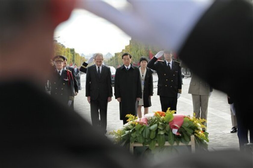 Chinese President Hu Jintao, center, stands next to French Junior Minister for Veterans' affairs, Hubert Falco, left, and a military official as he pays homage after laying a wreath at the unknown soldier's tomb, at the Arc of Triomphe, in Paris, Friday Nov. 5, 2010. The three-day state visit by Hu Jintao marks a dramatic turnaround from the tense ties of two years ago, when Sarkozy threatened to boycott the opening ceremony of the Beijing Olympics out of anger about China's treatment of Tibet. (AP Photo/Thibault Camus, Pool)