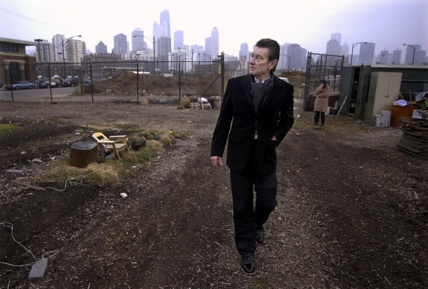 El arquitecto alemán Helmut Jahn camina por un lote vacío en el norte de Chicago, el 4 de marzo de 2004. Jahn, de 81 años, falleció tras ser impactado por dos vehículos cuando iba en su bicicleta, a las afueras de Chicago, se informó el 9 de mayo de 2021. (AP Foto/M. Spencer Green File)