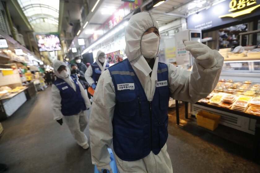South Korean workers wearing protective gear prepare to spray disinfectant as a precaution against the coronavirus at a market in Seoul.