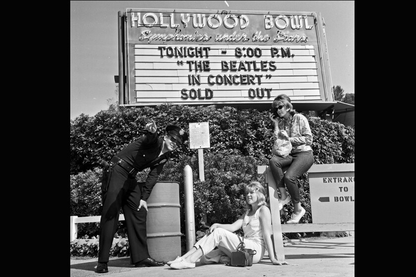 Officer Robert Yocum tells Beatles fans Chelie Mylott, center, and Melody Yapscott to move from their spot in front of the Hollywood Bowl on Aug. 23, 1964. They had no tickets but hoped to get them from scalpers or sneak in. This photo ran in the next day's Times.