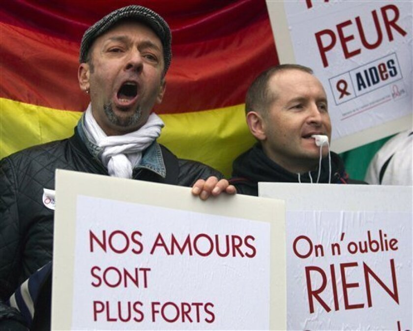 People demonstrate for equal rights with placards and flags in Paris, France, Wednesday, April 10, 2013. A gay rights watchdog group says that the number of reported homophobic acts has risen in France in recent weeks, amid nationwide protests over a bill under parliamentary debate that would legal