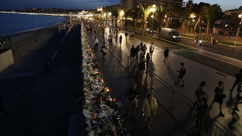 People walk on the Promenade des Anglais in Nice, France, on July 20, 2016, next to floral tributes, notes and candles placed in the road for victims of the deadly Bastille Day attack.