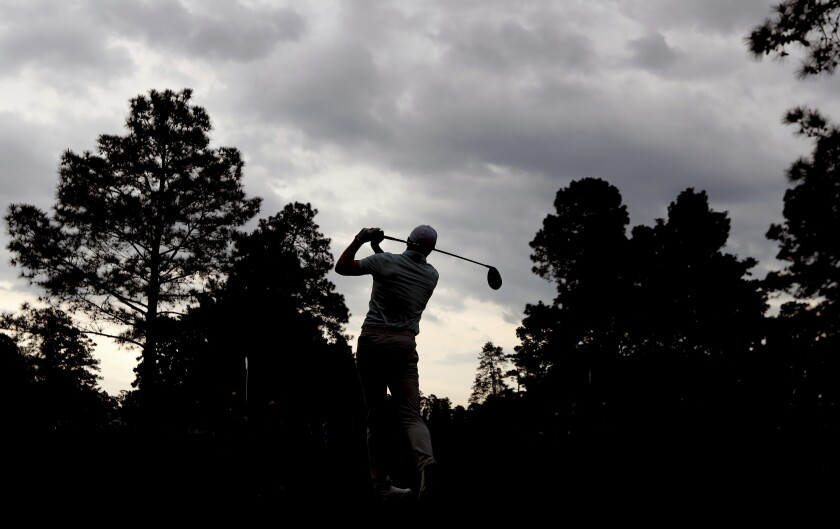 Storm clouds pass over as play resumes and Jordan Spieth tees off on the ninth hole during the third round of the Masters at Augusta National Golf Club on Saturday, April 10, 2021, in Augusta, Ga. (Curtis Compton/Atlanta Journal-Constitution via AP)