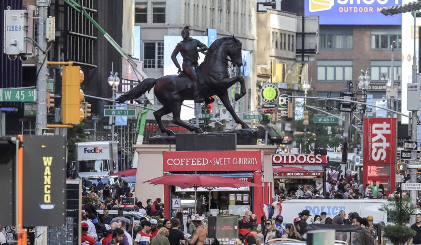"""FILE - In this Sept. 27, 2019 file photo, a bronze sculpture, """"Rumors of War,"""" by artist Kehinde Wiley, appears in Times Square in New York. Wiley's monumental bronze sculpture of a young black man astride a galloping horse is set to be permanently installed in Virginia's capital city, not far from the Confederate monument it mimics. An unveiling ceremony for """"Rumors of War"""" will be held Tuesday afternoon, Dec. 10 at the Virginia Museum of Fine Arts in Richmond. (AP Photo/Bebeto Matthews, File)"""