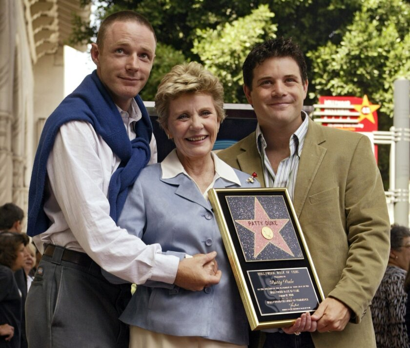 FILE - In this Aug. 17, 2004 file photo, Academy Award winner, and television actress Patty Duke poses with her sons, actors Mackenzie Astin, left, and Sean Astin after being honored with a star on the Hollywood Walk of Fame in Los Angeles. Duke, who won an Oscar as a child at the start of an acting career that continued through her adulthood, died Tuesday, March 29, 2016, of sepsis from a ruptured intestine. She was 69. (AP Photo/Damian Dovarganes, File)