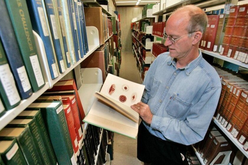 Peter Brueggeman, director of the Scripps Institution of Oceanography Library, shows one of the richly illustrated volumes that was digitized by Google Books and returned to the library.