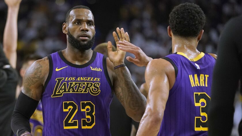 Los Angeles Lakers forward LeBron James (23) high-fives Josh Hart (3) at the end of the first half o
