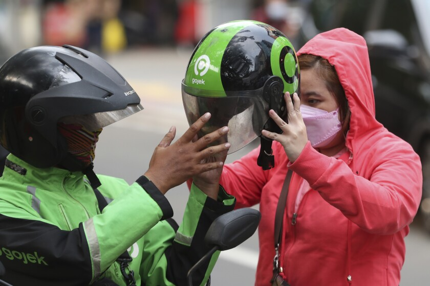 A Gojek driver gives a helmets to a customer in Jakarta, Indonesia, Monday, May 17, 2021. Indonesian ride hailing company Gojek and e-commerce firm Tokopedia said Monday that they are merging, in the largest ever deal in the country's history. (AP Photo/Achmad Ibrahim)