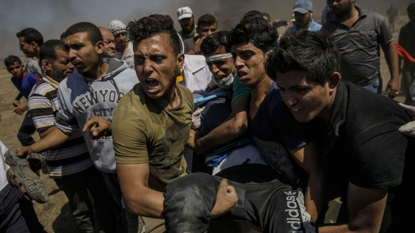 GAZA CITY, GAZA -- MONDAY, MAY 14, 2018: Protesters carry away the wounded shot by Israeli forces as