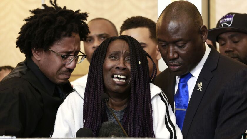 A tearful Sequita Thompson, center, discusses the shooting of her grandson, Stephon Clark, during a news conference on Monday.