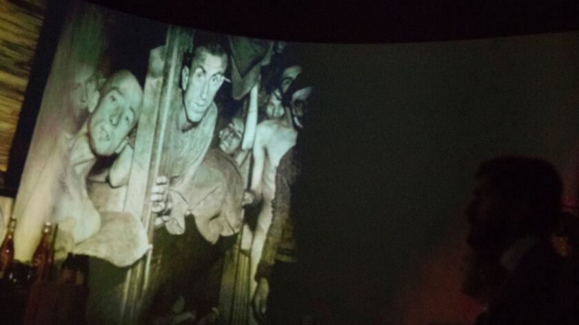 A projection of concentration camp survivors is on a screen as Prince Nasser bin Hamad al Khalifa of