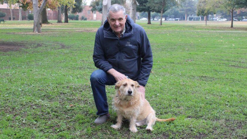 Leland Gilmore walks his dog, Ruff, at McKinley Park in Sacramento. The hazy skies don't bother hi