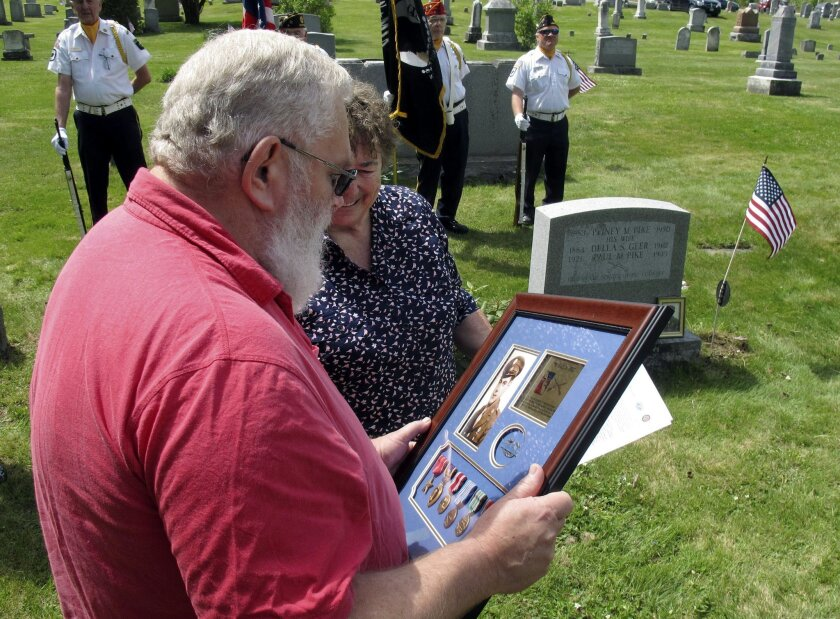Paul Pike, left, of Roxbury, Vt., looks at a Purple Heart and other medals earned by his father's cousin, also named Paul Pike, who was killed during World War II, that he was presented on Thursday, May 21, 2015, in Worcester, Vt. Audrey Richardson, partially hidden, of the Worcester Historical Society, watches during a ceremony arranged by the society and the organization Purple Hearts Reunited. (AP Photo/Wilson Ring)