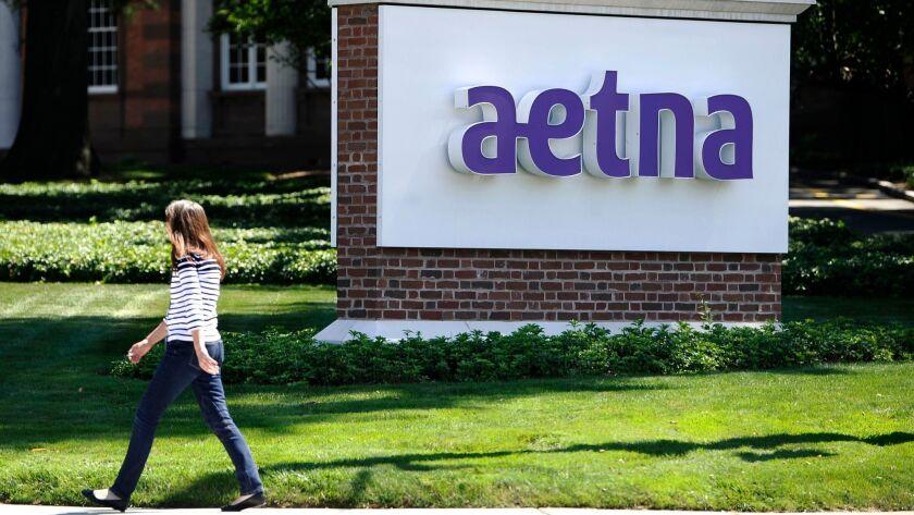 FILE - In this Tuesday, Aug. 19, 2014, file photo, a pedestrian walks past a sign for health insurer