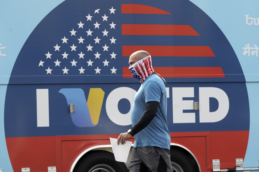 FILE - In this May 12, 2020 file photo, Robb Rehfeld wears a mask as he walks to cast his vote during a special election for California's 25th Congressional District seat in Santa Clarita, Calif. With a divided nation on edge as Election Day approaches, California is warning local election officials to prepare for disruption at polling places and potential cases of voters being intimidated or blocked from casting ballots. (AP Photo/Marcio Jose Sanchez, File)