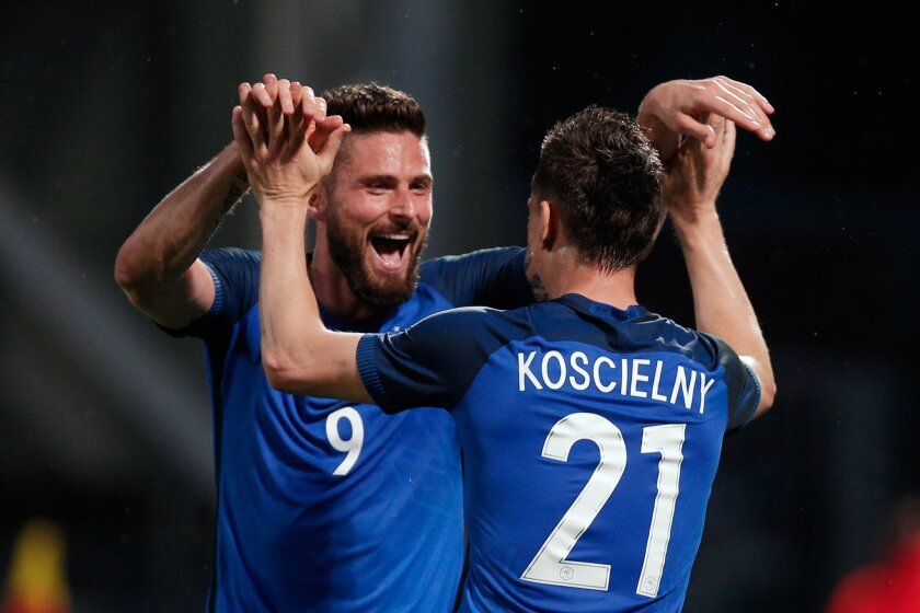 France's Laurent Koscielny celebrates with teammate France's Olivier Giroud, left, after he scored a goal during the friendly soccer match between France and Scotland at the Saint Symphorien Stadium in Metz, eastern France, Saturday, June 4, 2016. The French squad is in preparation for the EURO 201