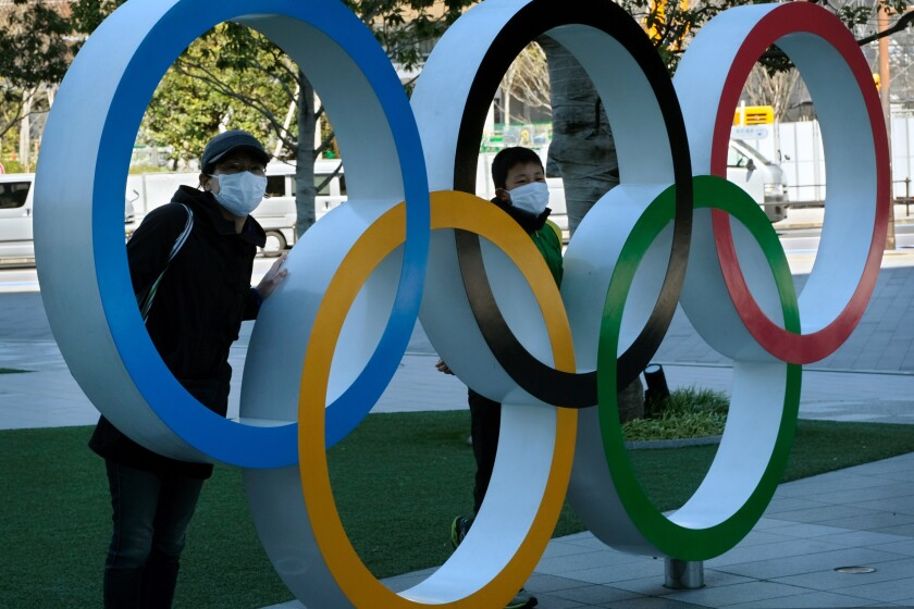 Two people pose at an installation of the Olympic rings in Tokyo on Tuesday. The IOC, Japanese Prime Minister Shinzo Abe and local organizers decided to postpone the Tokyo Games because of the coronavirus.