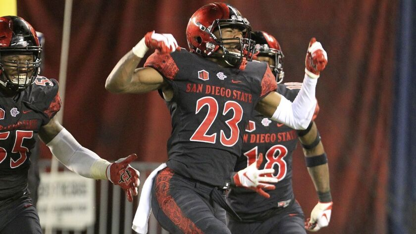 San Diego State cornerback Darren Hall celebrates with teammates after his interception in overtime positioned the Aztecs to beat Eastern Michigan on Sept. 22 at SDCCU Stadium. Hall added another interception in last week's win at Boise State.