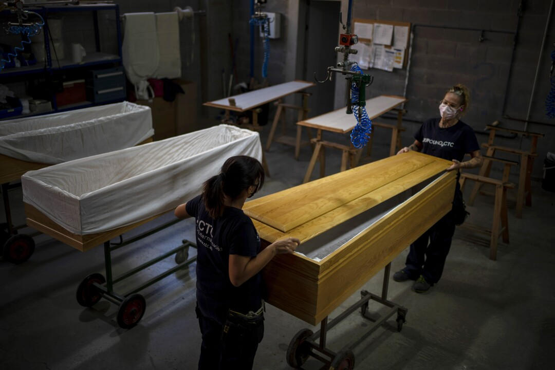 Employees work on coffins at the Eurocoffin factory in Barcelona, Spain.