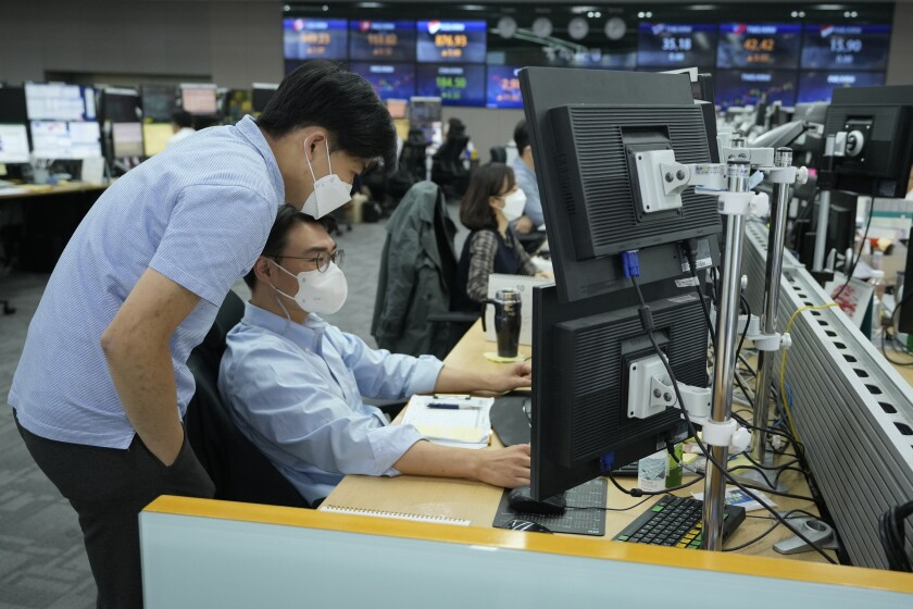 Currency traders watch monitors at the foreign exchange dealing room of the KEB Hana Bank headquarters in Seoul, South Korea, Friday, Oct. 8, 2021. Asian stocks followed Wall Street higher Friday after U.S. lawmakers temporarily averted a possible government debt default while investors waited for American jobs numbers. (AP Photo/Ahn Young-joon)