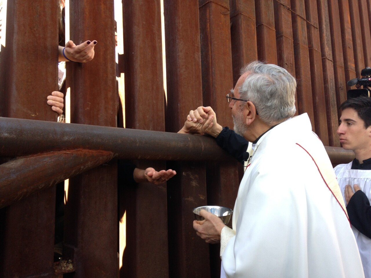 Tucson Bishop Gerald Kicanas gives Communion to people on the Mexican side of the border fence.
