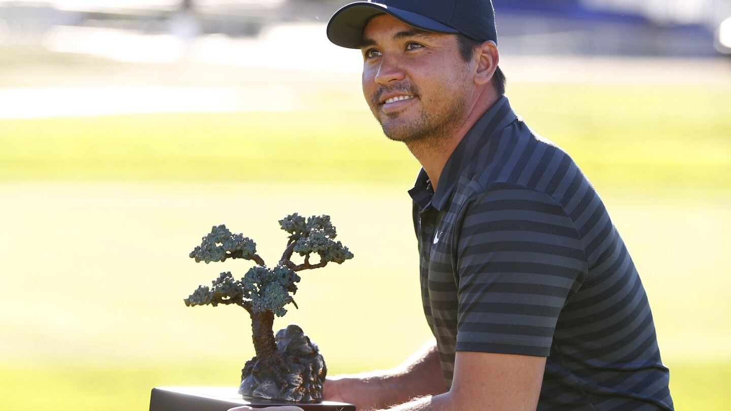 Jason Day poses with the trophy after winning Farmers Insurance Open at the Torrey Pines Golf Course on January 29, 2018. Day beat Alex Noren in a playoff. (Photo by K.C. Alfred/ San Diego Union-Tribune)