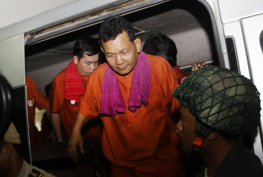 Suth Vanny, center, and Chay Sarith, left, suspected attackers who are accused of beating two opposition lawmakers, arrive at Phnom Penh Municipal Court in Phnom Penh, Cambodia, Friday, May 27, 2016. The court on Friday convicted three military commandos, including them, of beating up two oppositio