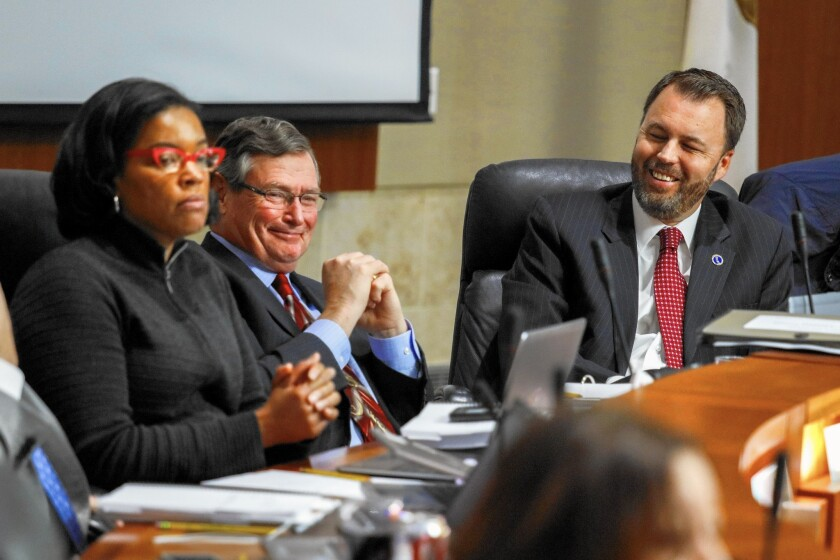 """Cal State Chancellor Timothy P. White, center, at a meeting in March. """"We're actually very pleased about what we were able to craft,"""" White said of the deal announced Friday."""