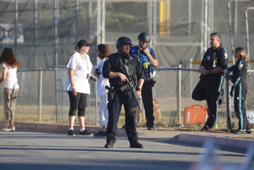 A police officer stands guard outside Gilroy High School, near the site of a mass shooting