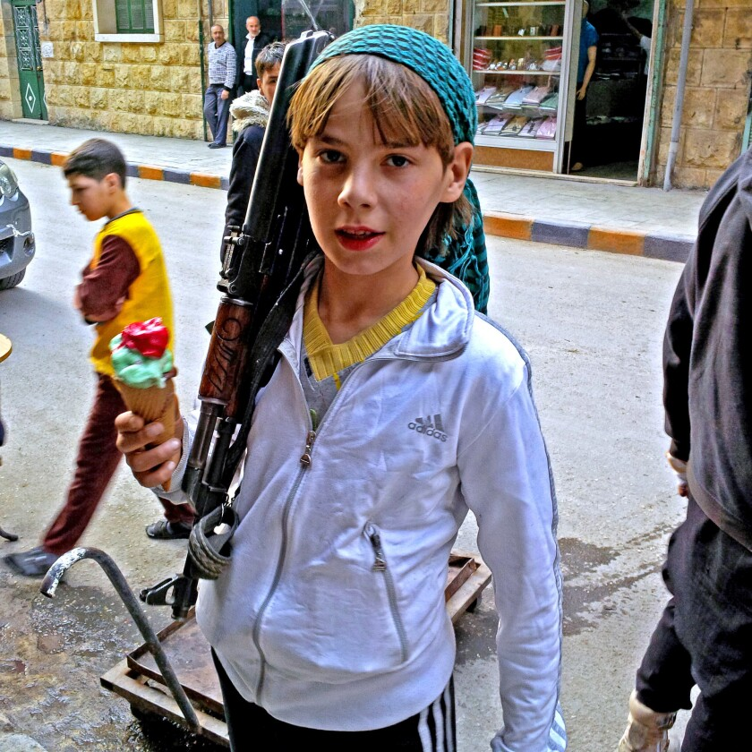 An armed boy in Aleppo, Syria, says he is a fighter with the Suqoor al Sham rebel group. He claimed to have been born in 1989, making him 24 or 25.