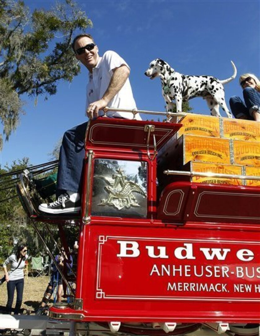 In this image provided by HHP Photo, NASCAR driver Kevin Harvick and Budweiser Clydesdales ride on the way to deliver beer and Daytona 500 tickets to Justin Ryter and Jason Ryter, twin brothers who completed four years of active duty in the United States Marine Crops and recently returned home, Wednesday, Feb. 20, 2013, in Daytona Beach, Fla. (AP Photo/HHP Photo, Harold Hinson) MANDATORY CREDIT; NO SALES
