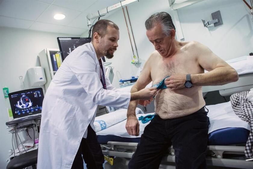 El doctor Jorge Pagola, investigador del VHIR, coloca al paciente Meriton Bacuña, un chaleco Holter -aparato que registra la actividad del corazón- para detectar la causa de los ictus en un grupo de pacientes que padecen fibrilación auricular, un tipo de arritmia muy difícil de localizar. EFE/Archivo
