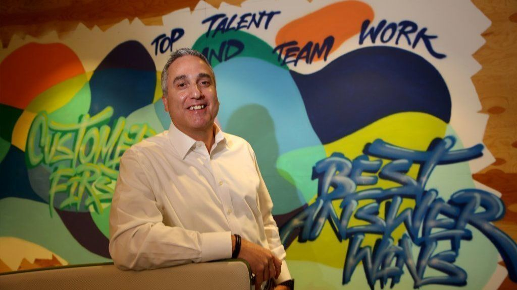 Joe DeCosmo, chief analytics officer of Enova International, stands by one of the murals in the company's Chicago Loop office. Enova brought on 128 new people in 2017, raising its total employee count to 1,145.