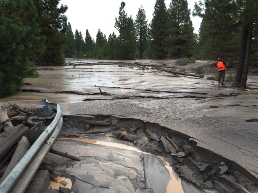 Officials assess road damage caused by a mudslide down Mt. Shasta on Saturday.