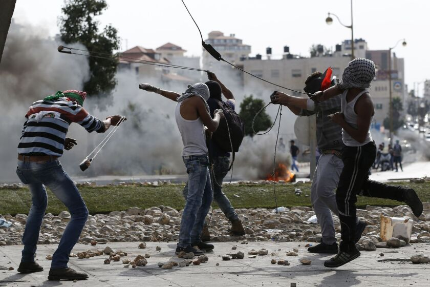 Palestinian protesters use slingshots to launch stones toward Israeli security forces