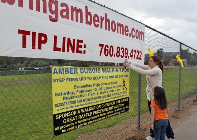 Sunday at Escondido High School,  Jamie Clayton and her daughter Brianna, 5, came to pay respects, leaving a potted flower and signing the banner to bring Amber Dubois home.