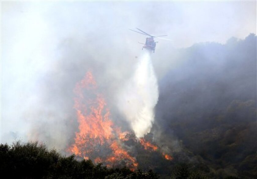 A firefighting helicopter makes a water drop on a brush fire near the Getty Center art complex Wednesday, July 8, 2009 in Los Angeles. The Getty Center art complex and nearby Mount St. Mary's College were evacuated Wednesday as a brush fire burned on slopes of the Santa Monica Mountains near the Getty's parking area facilities. (AP Photo/Nick Ut)