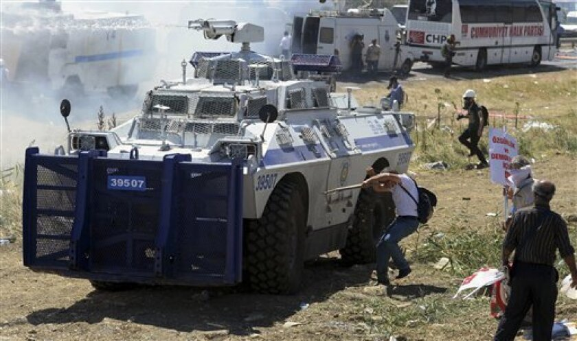 Protesters clash with riot and paramilitary polices as they fire tear gas and use water cannons to disperse them outside the Silivri jail complex in Silivri, Turkey, Monday, Aug. 5, 2013. Some 275 people - including military officers, politicians and journalists - are facing verdicts in a landmark and divisive trial in Turkey over an alleged conspiracy to overthrow the government. The court has acquitted 21 people accused of plotting to overthrow the Islamist-rooted government in the five-year